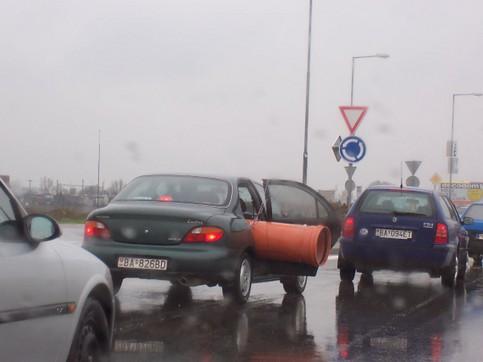 Ein Auto transportiert ein Rohr, das aus der Seite hervorsteht.