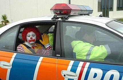 Ronald McDonald wurde verhaftet, sitzt auf dem Rücksitz eines Polizeiautosund winkt traurig aus dem geöffneten Fenster heraus.