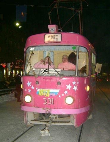 Zwei alte Frauen mit rosa Pullovern im Führerhäuschen einer rosa Tram.