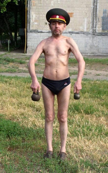 Ein halbnackter Russe hebt Gewichte hoch.