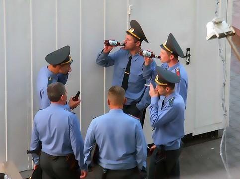 Russische Polizisten trinken gemeinsam Bier aus Flaschen.