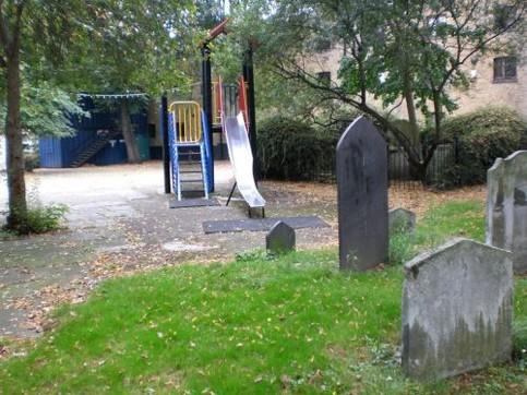 Ein Kinderspielplatz mit Rutsche ist direkt neben einem Friedhof gebaut.