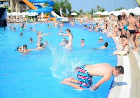 Ein Foto aus einem Schwimmbad. Ein Mann scheint einen Salto vom Beckenrand zu machen. Es sieht dabei so aus, als würde er gleich mit dem Kopf auf dem Rand aufschlagen.