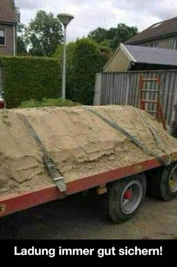 """Ein flacher Anhänger wurde mit Sand beladen, der sinnloserweise mit Spanngurten gesichert wurde. Dazu steht der Text: """"Ladung immer gut sichern!"""""""