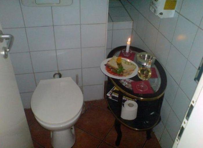 In einem Bad stehen nebem dem WC auf einem Tischchen Sandwichs und ein Glas Wein. Dazu brennt eine Kerze.