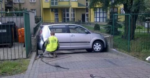 Ein Auto ist in einer Einfahrt quer zwischen Betonwänden eingeklemmt.