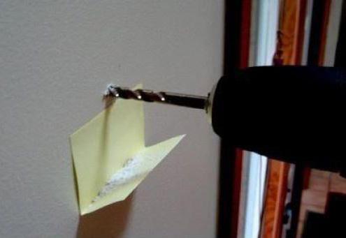 Ein Loch wird mit einem Bohrer in eine Wand gebort. Dabei wurde unter dem Bohrer ein geknicktes Post-It an die Wand geklebt. So fällt kein Staub auf den Boden, sondern wird vom Post-It aufgefangen.