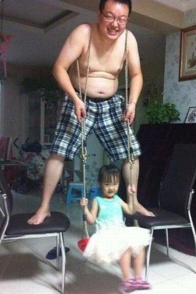 Ein Vater steht auf zwei Stühlen und hat eine Schaukel über seine Schultern gehängt. Auf der Schaukel schaukelt ein kleines Kind.