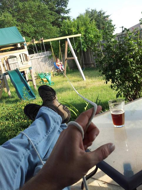 Ein Mann fotografiert sich selber, während er seine Tochter mit einer langen Schnur schaukelt und dabei Bier trinkt.