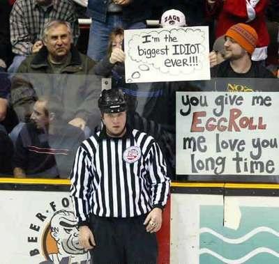"""Ein Mann hält hinter einem Eishockey-Schiedsrichter ein Schild hoch: """"I'm the biggest IDIOT ever!!!""""."""