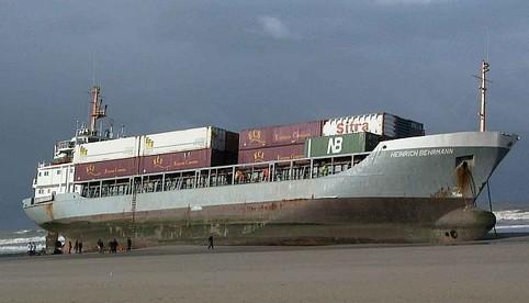 Ein Containerschiff ist an einem Strand gestrandet.