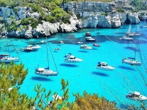 Viele Yachten und Boote liegen in einer Bucht und werfen ihre Schatten auf den Meeresgrund. Das Wasser ist so klar, dass es aussieht, als würden die Schiffe schweben.
