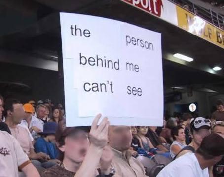 """Ein Junge hält in einem Stadion ein Schild hoch: """"the person behind me can't see""""."""