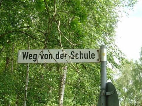 """Ein Straßenschild, die Straße heisst """"Weg von der Schule""""."""