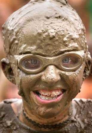 Ein Junge mit Schlamm im Gesicht und einer Zahnspange.