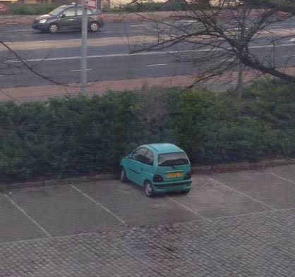 Ein Auto steht auf einem leeren Parkplatz so, dass es zwei Parkpläte benötigt.