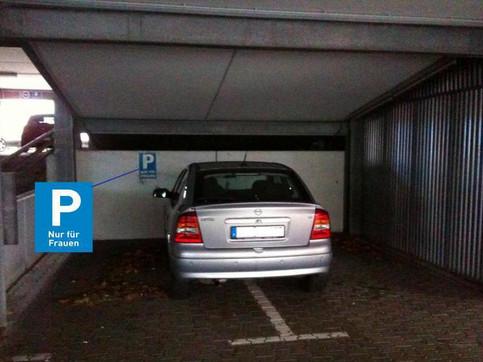 Auf einem Frauenparkplatz steht ein Auto genau in der Mitte zwischen zwei Parkplätzen.