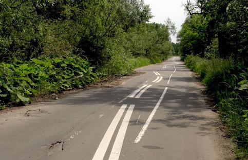 Die Fahrbahnmarkierungen auf einer Straße sind krumm und quer.