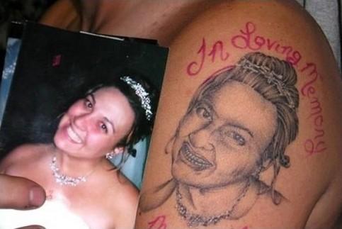 Ein Tattoo auf einem Oberarm, das unglaublich schlecht ist, zeigt eine lächelnde Frau.