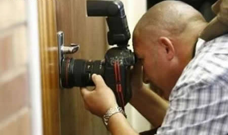 Ein Mann schaut mit seiner Fotokamera durch ein Schlüsselloch.