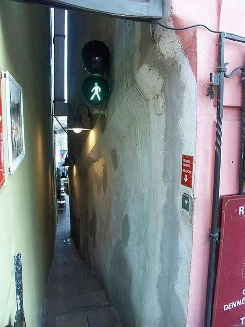 Ein Fußgängerweg ist so schmal und eng, dass eine Ampel installiert wurde.