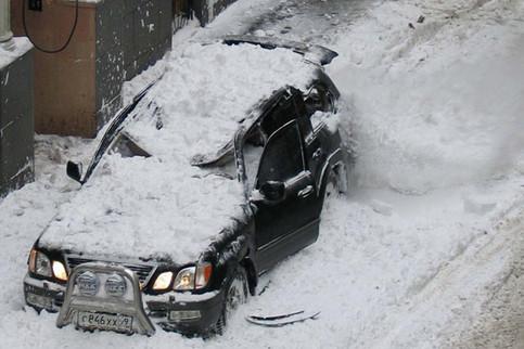 Ein Auto ist durch eine Schneelawine von einem Hausdach zerstört worden.