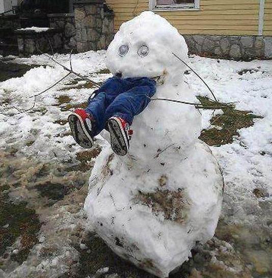 Ein Schneemann wurde so gebaut, als würde er ein Kind fressen. Aus seinem Mund schauen Beine in Hosen und Schuhen heraus.