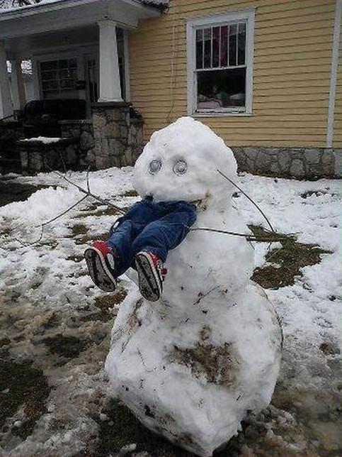 Ein Schneemann in einem Vorgarten ist so gebaut, dass er einen Menschen gefressen zu haben scheint. Aus seinem Mund schaut eine Jeans mit Schuhen heraus.