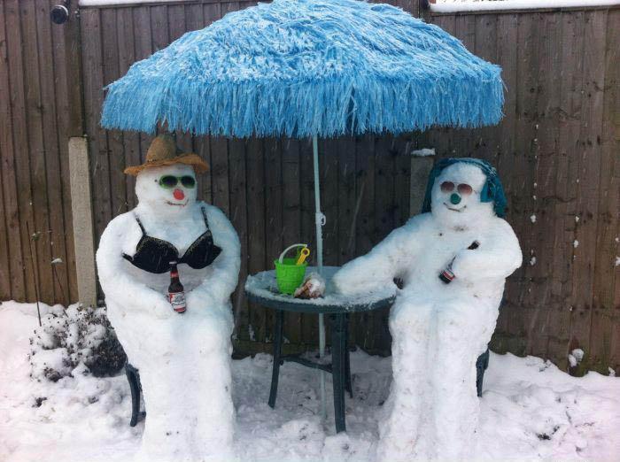 Zwei Schneemänner sitzen gemütlich auf Stühlen an einem Tisch und haben jeder eine Flasche Bier.