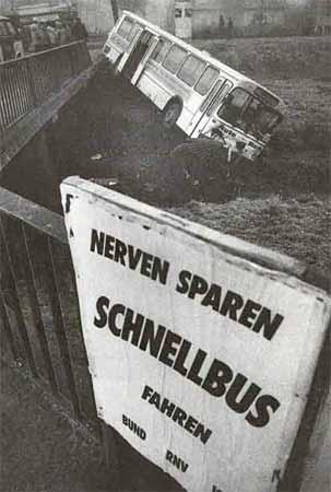 """Ein Schild """"Nerven sparen - Schnellbus fahren"""", im Hintergrund ein verunglückter Bus."""