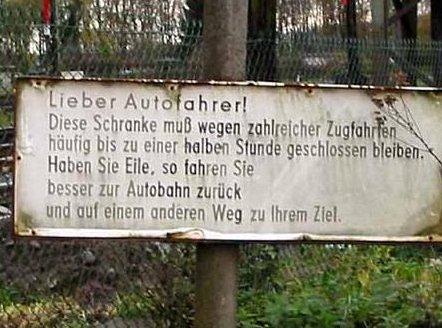Ein Schild weist darauf hin, dass eine Schranke häufig lange geschlossen bleibt und man daher lieber zurück zur Autobahn fahren soll.