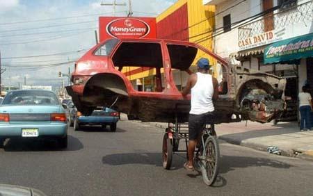 Ein Autowrack wird auf einem Fahrrad transportiert.