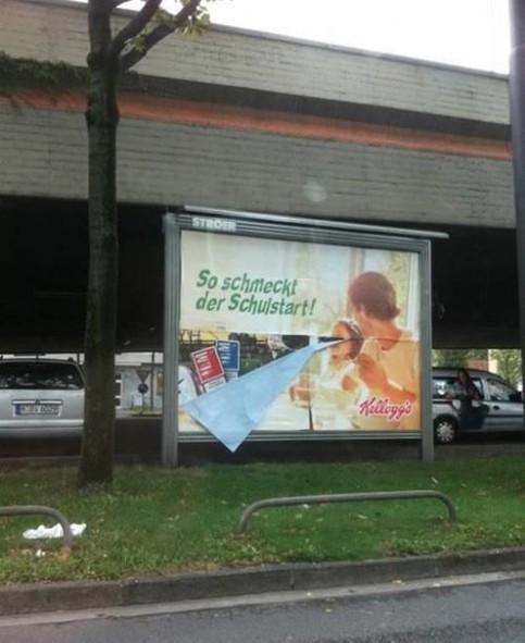 """Auf einer Plakatwand ist ein Werbung für Cerealien für Kinder aufgeklebt. Dazu der Spruch """"So schmeckt der Schulstart"""". Eine Ecke des Plakates hängt runter. Darunter sieht man Werbung für Zigaretten."""