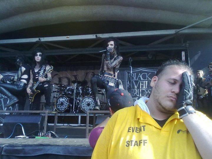 Ein Mann von der Konzert-Security hält genervt eine Hand vors Gesicht, während im Hintergrund eine Metal-Band auf einer Bühne spielt.