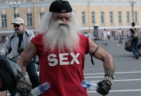 """Ein Mann mit Vollbart macht eine Pose, auf seinem T-Shirt steht """"Sex""""."""