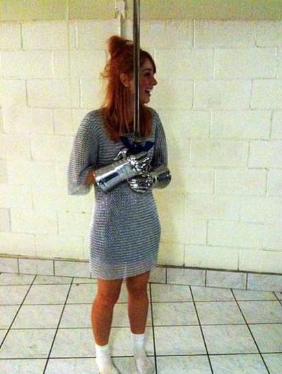 Eine junge Frau trägt ein Kettenhemd und hält ein Schwert in den Händen.
