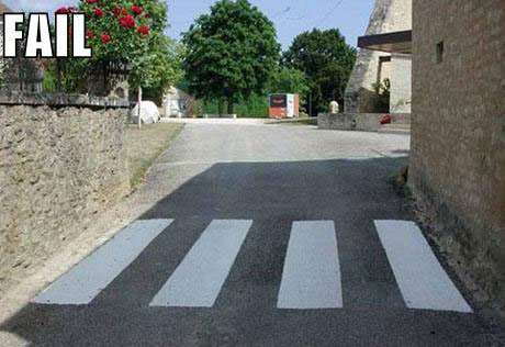 Ein Zebrastreifen ist auf einer Strasse aufgemalt, die gar keinen Bürgersteig hat.