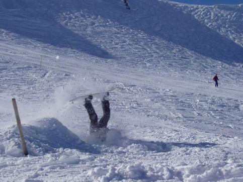 Ein Snowboarder landet mit dem Kopf im Schnee.