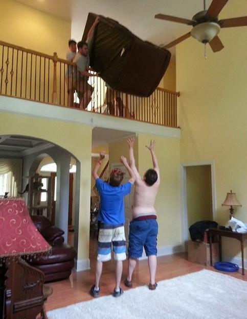 Mehrere junge Männer wollen ein Sofa von einer Emport herunterreichen. Das wird mit Sicherheit schief gehen.