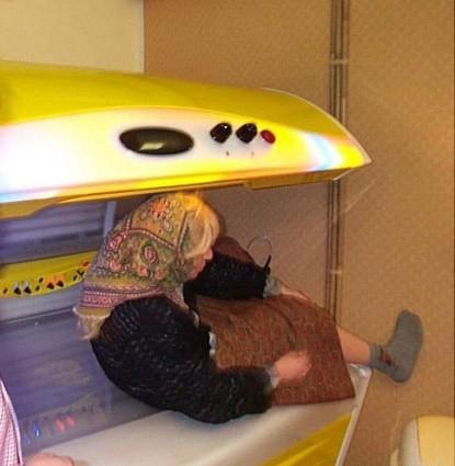 Eine Frau mit Rock und Kopftuch liegt unter einem Solarium