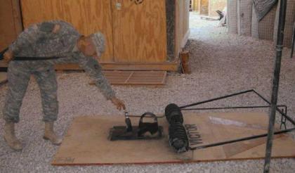 Ein Soldat vor einer Mausefalle, groß genug für einen Menschen.