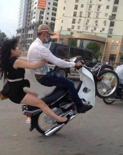 Ein junger Mann macht mit einem Roller einen Wheelie. Eine junge Frau sitzt hinter ihm, sie stürzt bei dem Wheelie nach hinten ab.