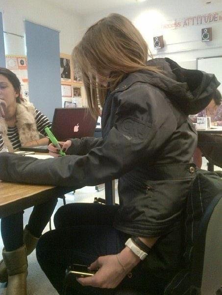 Ein Mädchen spickt während eines Tests in der Schule auf ihrem Handy durch eine trickreiche Art und Weise.