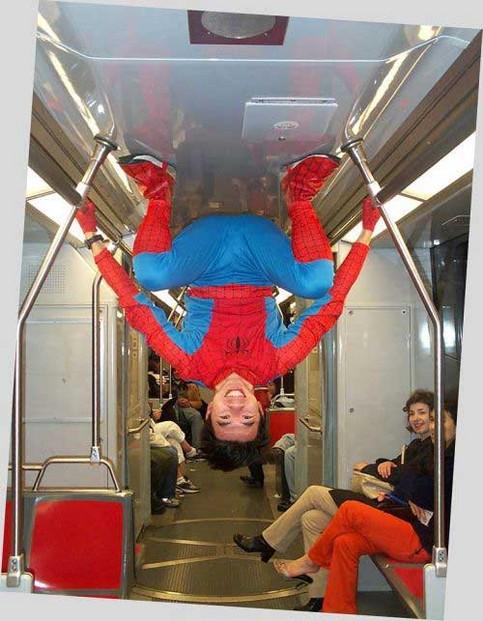 Spiderman in der U-Bahn. Ein Mann mit Spiderman-Kostüm hängt an der Decke.