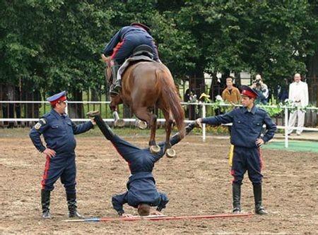 Ein Pferd springt über einen Mann, der mit dem Kopf nach unten anstelle eines Hindernisses fest gehalten wird.