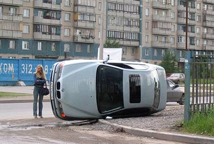 Ein Frau neben einem umgekippten Auto.