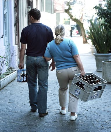 Ein Mann und eine Frau: sie schleppt eine Kiste Bier, er nur ein Sixpack.