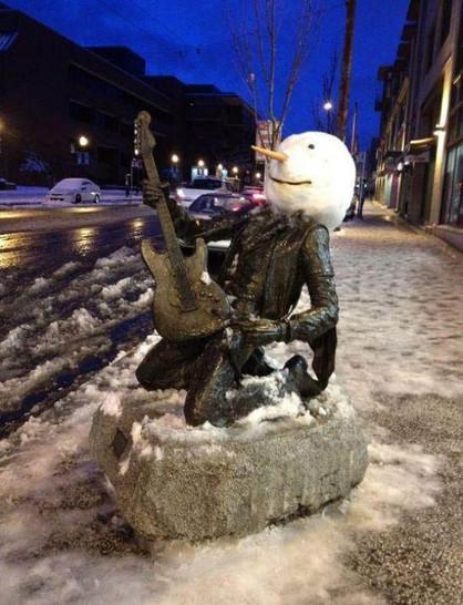 Eine Statue wurde mit einem Kopf aus Schnee umgebraut. Sie hat eie Gitarre in den Händen und rutscht auf den Knien.