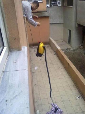 Ein Mann holt ein Kleidungsstück aus einem Fenster, indem er einen Staubsauger aus dem Fenster hängt und den Stoff ansaugt.