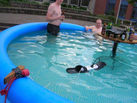 In einem Pool schwimmt eine Steckdosenleiste, befestigt auf zwei treibenden Schlappen.